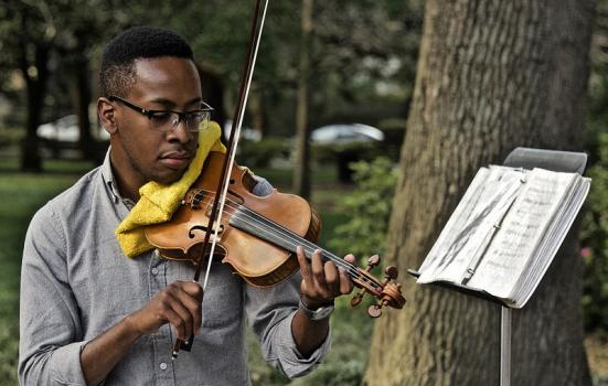 Man playing a violin in a park