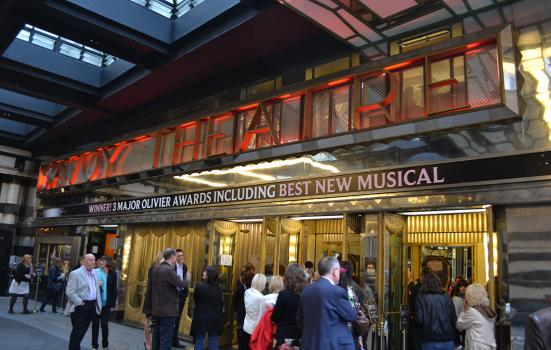 people standing casullay outside the Savoy Theatre in London