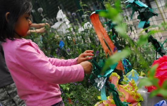 A girl in a garden with coloured paper artwork