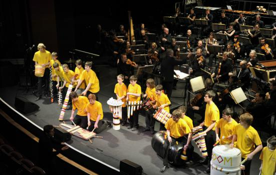 Young people in yellow t-shirts performing at a concert