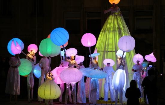Photo of dancers in brightly lit colours in nighttime show