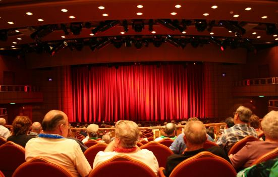 An audience including older people in a theatre auditorium