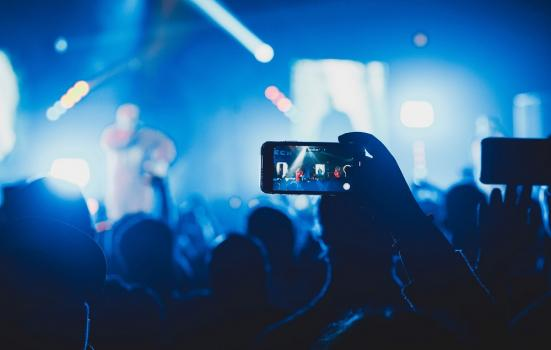 A photo of a smartphone being held up in a concert audience