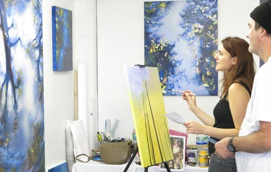 Photo of a woman painting in a studio