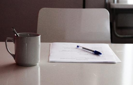 Photo of paper on a table with a pen and mug