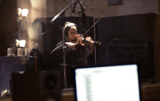 Photo of woman playing a violin in a recording studio