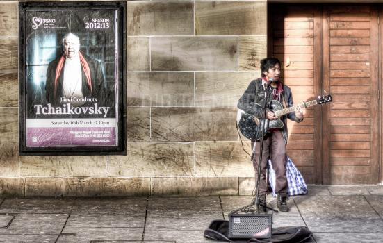 Photo of busker in front of classical concert poster