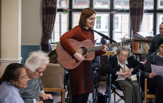 Musician playing a guitar in a care home