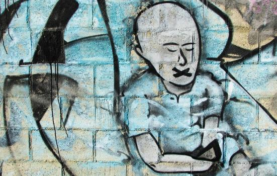 Street art showing a man with a cross in place of a mouth