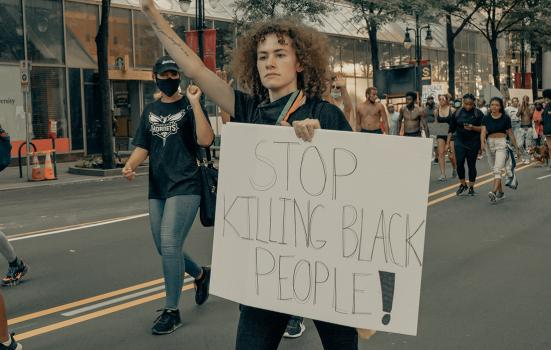 woman marching with banner 'stop killing black people'