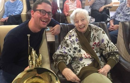 Photo of musician with large brass instrument and older person