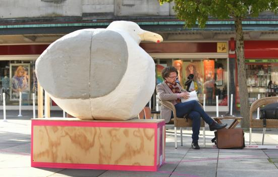 Statue of a large seagull with a man sitting crossed legged on a bench reading in the background