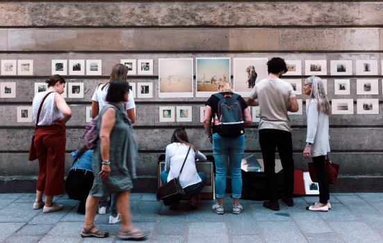 group of people looking at art on a wall outside