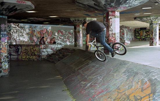 cyclist at a skate park covered in graffiti