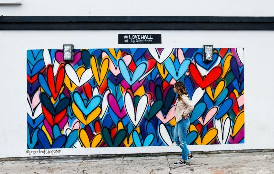Woman walking past graffiti of multicoloured hearts