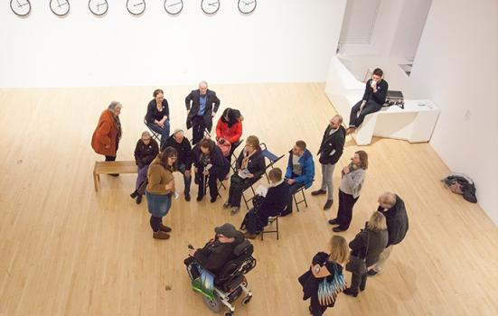 A group of people including a wheelchair user in an art gallery