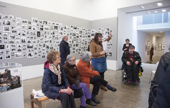 A gallery tour including people sitting down and a wheelchair user