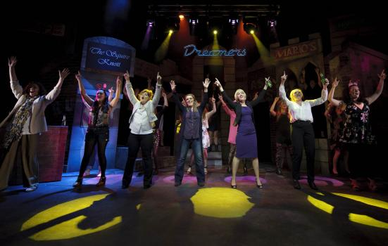 Photo of performers on stage with arms raised