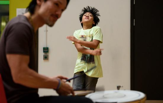 Photo of drummer and young boy dancing