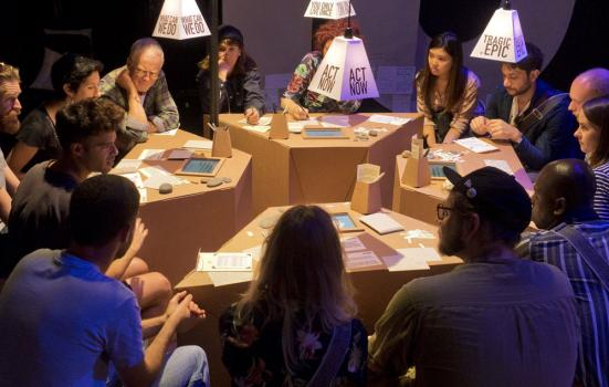Photo of an interactive installation, a group of people meet around cardboard tables