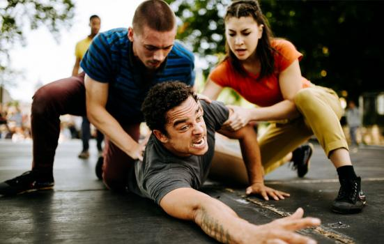 Photo of two actors holding back a third who, while lying on the ground, is reaching out into the distance in apparent pain.