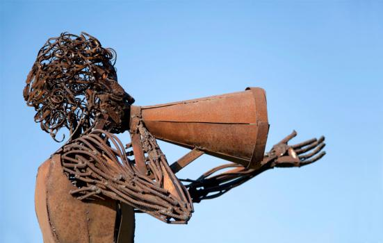 Photo of a cast iron sculpture of a woman using a megaphone