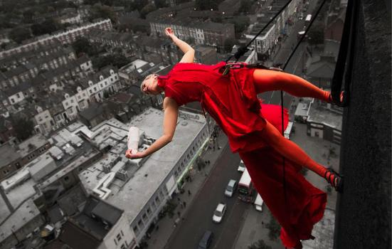 Photo of a woman suspened on the side of a building, in a red dress, over a grey city landscape