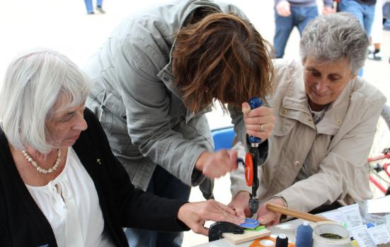 Photo of three woman building crafts, one using a handheld deal