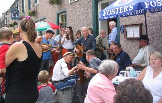 Photo of people playing music outside a pub