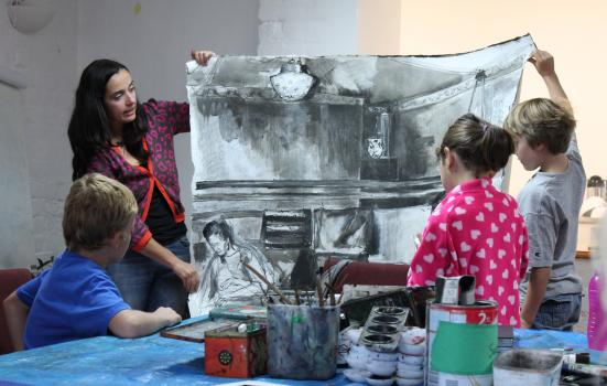 Photo of teacher with children holding up large drawing