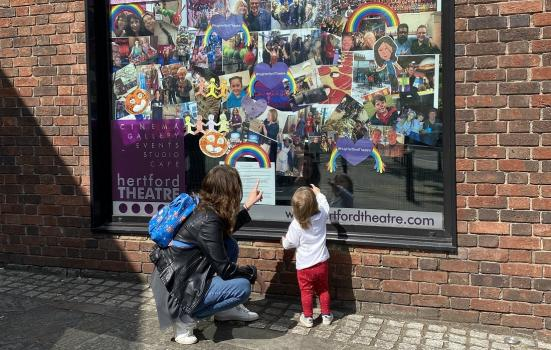 Mother and daughter looking at a window display at Hertford Theatre