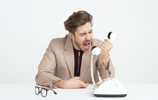 Photo shows a youngish man screaming into a telephone in apparent frustration