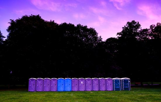 a row of portable toilets in a field, photo taken at twilight