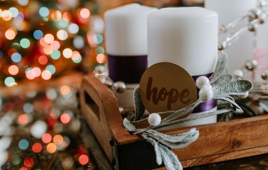 Candle with a brown card label saying hope attached, christmas decorations in the background