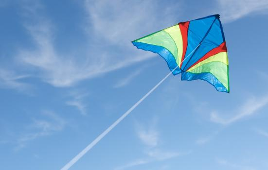 Photo of kite flying against blue sky