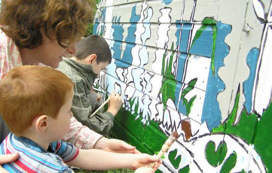 Photo of a woman and children painting a mural