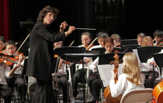 Conductor leading a school orchestra