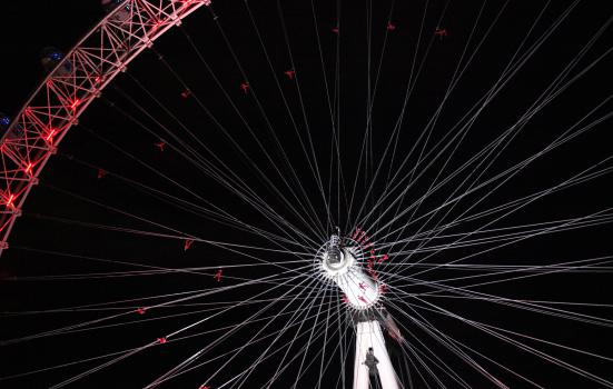 A picture showing people in red suits climbing the London Eye