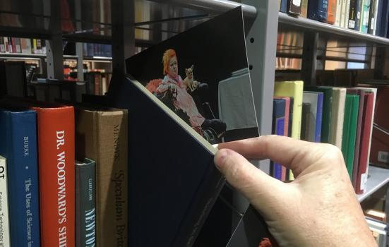 Photo showing a postcard being placed in a book on a bookshelf