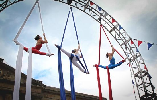 Photo of three aerial silk performers