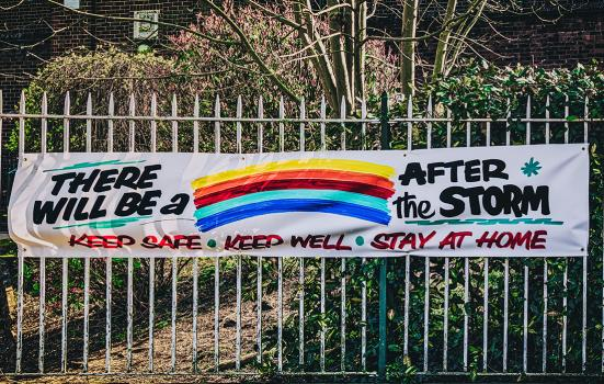 "banner on railings with the words ""there will be a rainbow after the storm"" (the word 'rainbow' is replaced with a painting of a rainbow)"