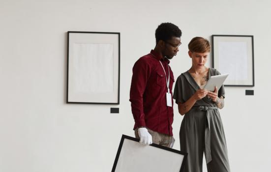 Two people in a gallery looking at a tablet