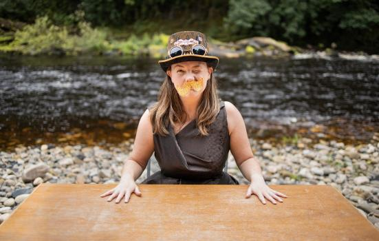 Lisette, a white woman with freckles and long brown hair, sits behind a wooden table, her hands spread out on its top. She is wearing a brown dress, a top hat and a yellow paper moustache. She is winking. The table is on a pebble beach with a river running behind it. Image credit: Rob Irish.