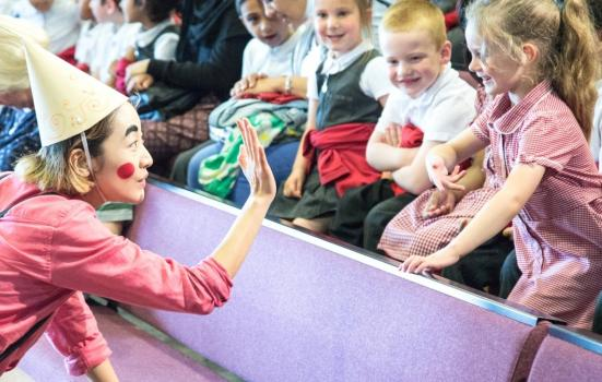 Photo of performer high-fiving young girl in audience