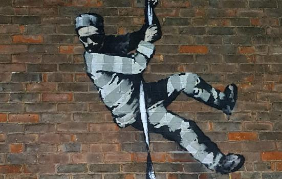 Black and white stencil graffiti of a prisoner escaping down a wall