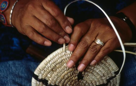 A close-up shot of a person's hands weaving a basket