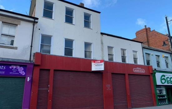 A highstreet scene with closed shops put up for let
