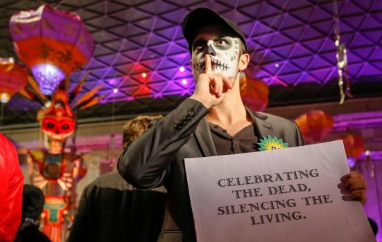 Face-painted man with sign: 'Celebrating the dead, silencing the living'