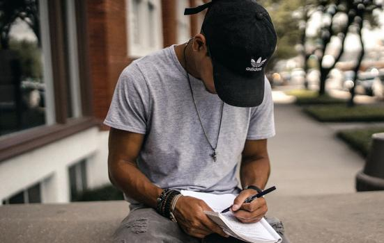 Person in balck adidas cap sitting on a bench writing in a notebook