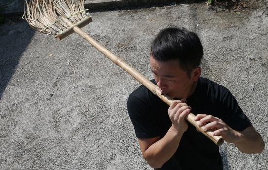 Photo of a man playing a broom converted into a flute